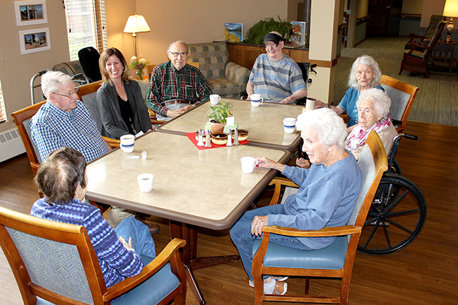 residents of an assisted living facility gathered around a table talking and drinking coffee