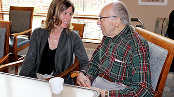 Director of an assisted living facility talking with a resident