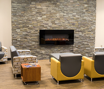 A fireplace and chairs at the New Richmond campus