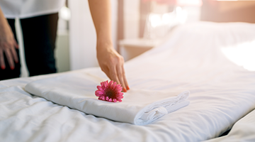 A hospitality specialist placing a flower on a pillow in a hotel room