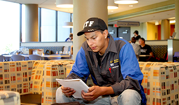 Student wearing automotive uniform studying a paper