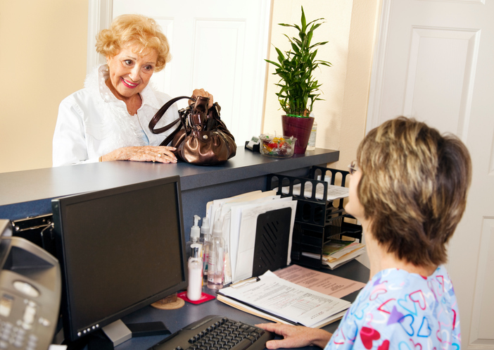 A healthcare receptionist greeting a guest