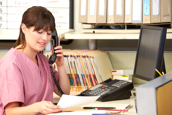A medical professional talking on the phone at a desk with folders behind her