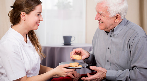 Dietary Manager handing a cookie to an aging adult