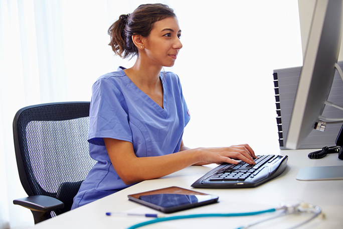 A medical office professional wearing nursing scrubs and sitting at a computer at a front desk