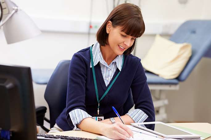 A medical office professional sitting at a desk in a doctor's office