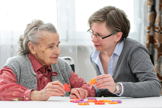 A personal care worker assisting an aging adult with a puzzle