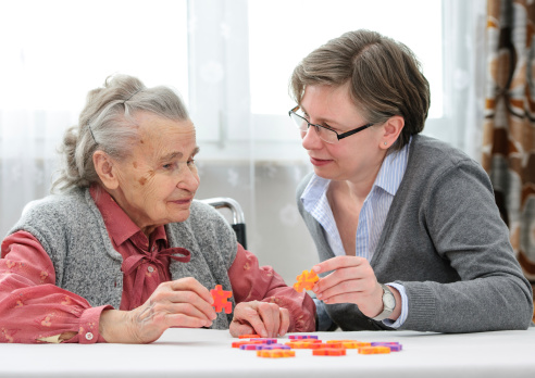 A caregiver doing a puzzle with an aging adult