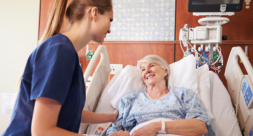 A nurse talking to a senior patient in a hospital bed