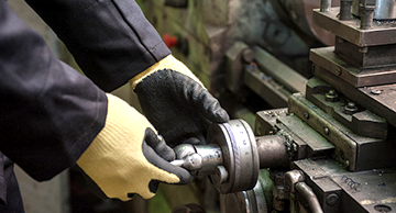 Close up of a hand wearing protective gloves and working on a machine
