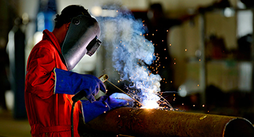 A worker welding a pipe