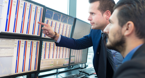 Two financial analyst looking at stocks on a computer screen