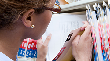 A health information technician looking through a medical record folder