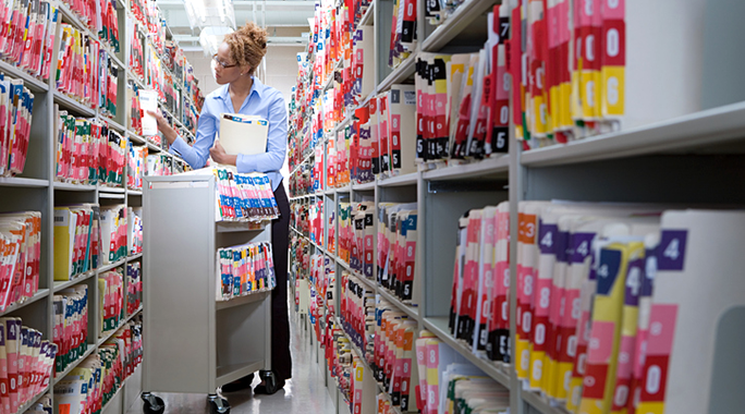 A health information technician walking through an aisle of file folders