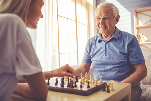 A caregiver playing chess with an aging adult