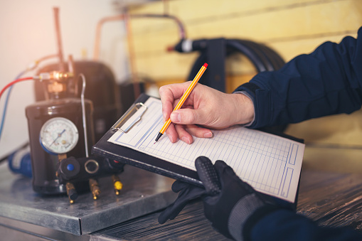 Residential HVAC/R Technician analyzing an air conditioning unit