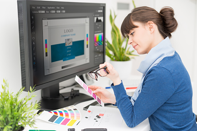 A graphic designer looking at color samples at a computer