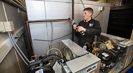 An HVACR student doing hands-on work