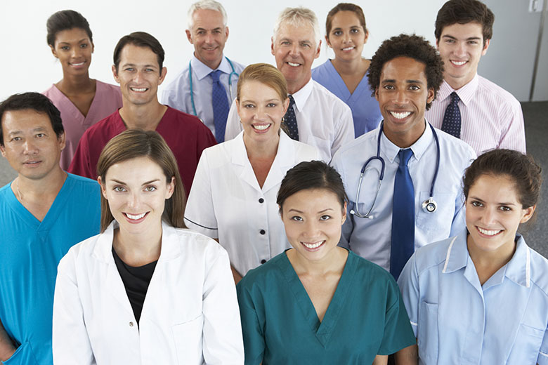 11 healthcare professionals dressed in colorful scrubs or professional wear,  standing in a group and smiling