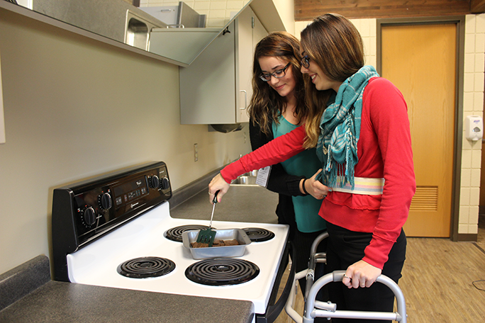 Students practicing the skills to assist someone in the kitchen