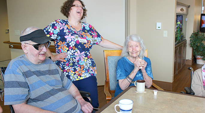 A caregiver at a CBRF laughing with residents
