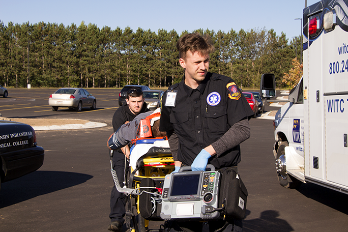 An Emergency Medical Technician in training, carrying a stretcher