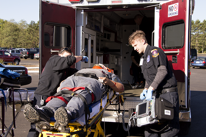 Paramedic students practicing loading a stretcher into an ambulance