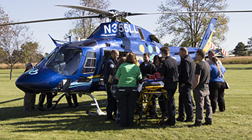 A group of students gathered around a helicopter