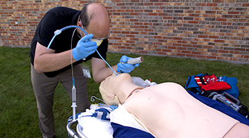 An EMT student using the tools of the trade to simulate a real life scenario
