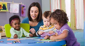 A toddler caregiver looking at the artwork of three toddler-aged kids in a school-like setting