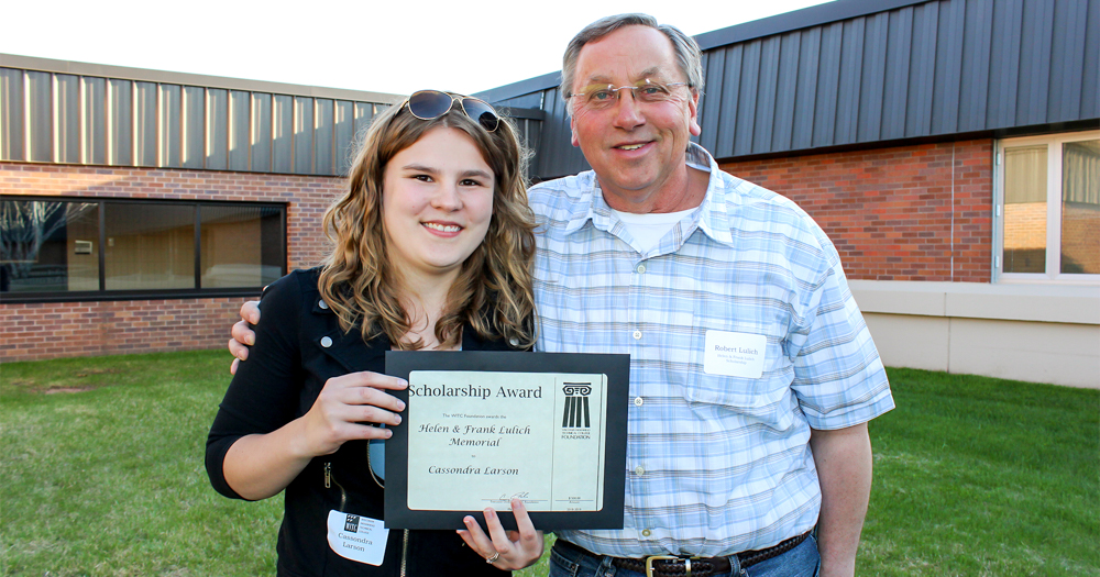 Female student standing outside holding a scholarship plaque. She is standing next to the man who is the scholarship donor.