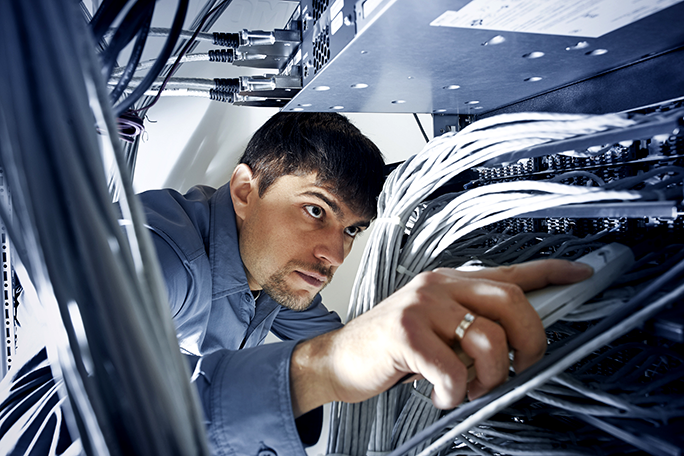 A broadband professional checking server's wires in data center