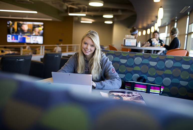 Student studies on a computer and smiles at the camera in a modern student lounge setting with bright windows