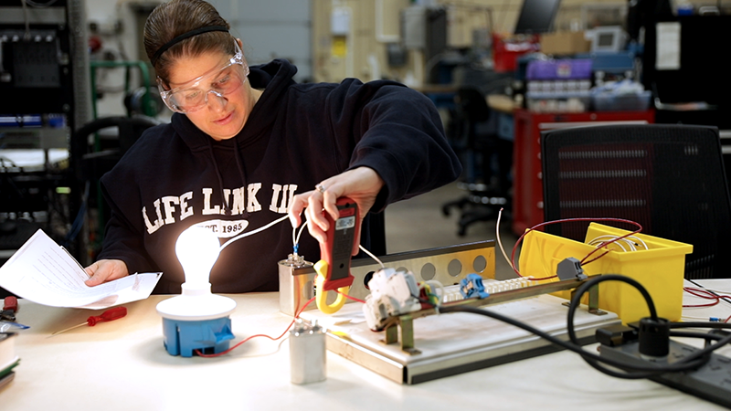 Young female student work on a light bulb in the Automation program