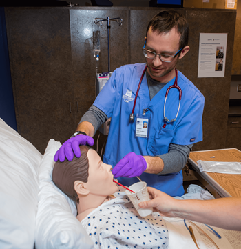 Male student works with simulation equipment in the Nursing program