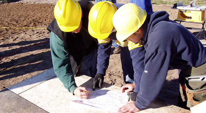 Three construction workers looking at a blueprint