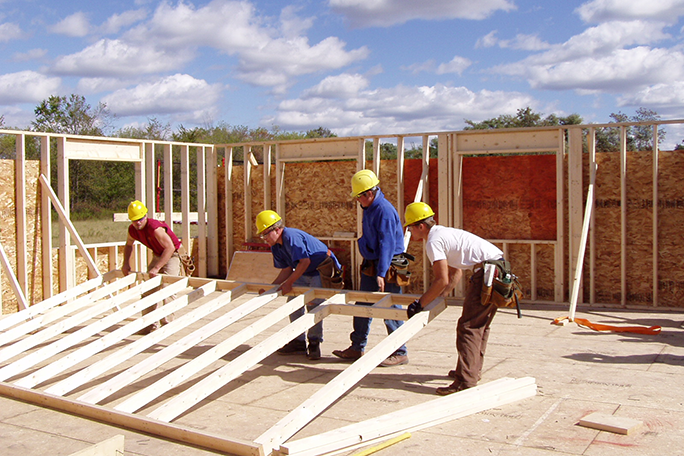 Construction students building a house