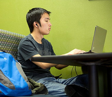 Young, male student working on his computer in a booth on campus with headphones in.