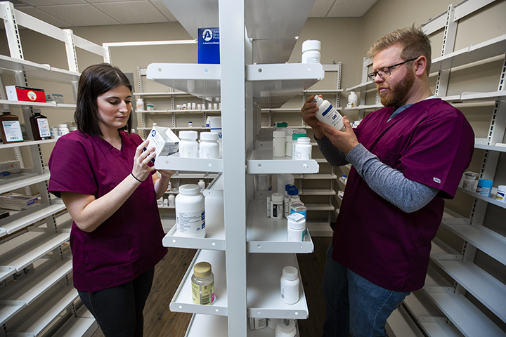 2 pharmacy technicians looking at shelves of medications
