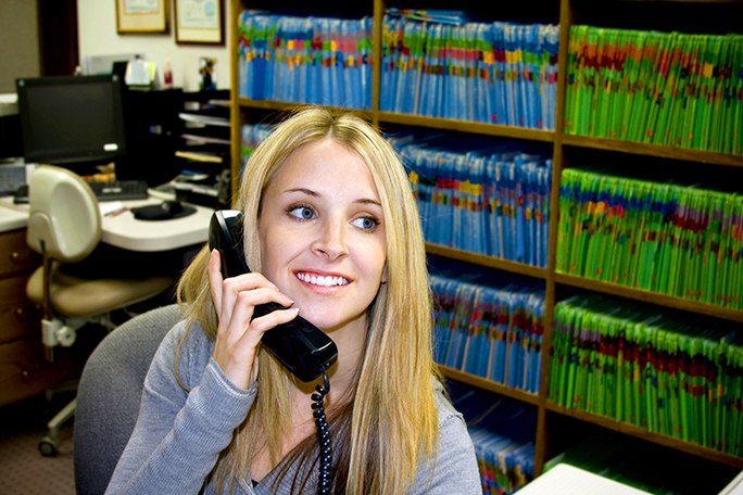 A medical office professional on the phone at the front desk