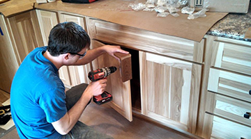 A student working on drilling cabinets