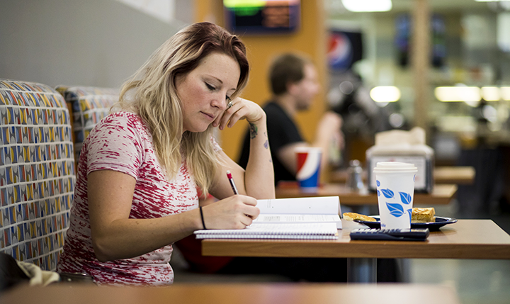 Student studying at a table in The Hub