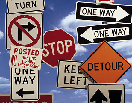 A variety of traffic signs including stop, detour, one way, keep left, and no right turn.