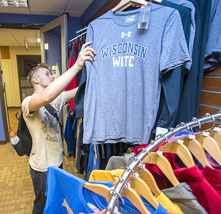 A student browsing through WITC t-shirts