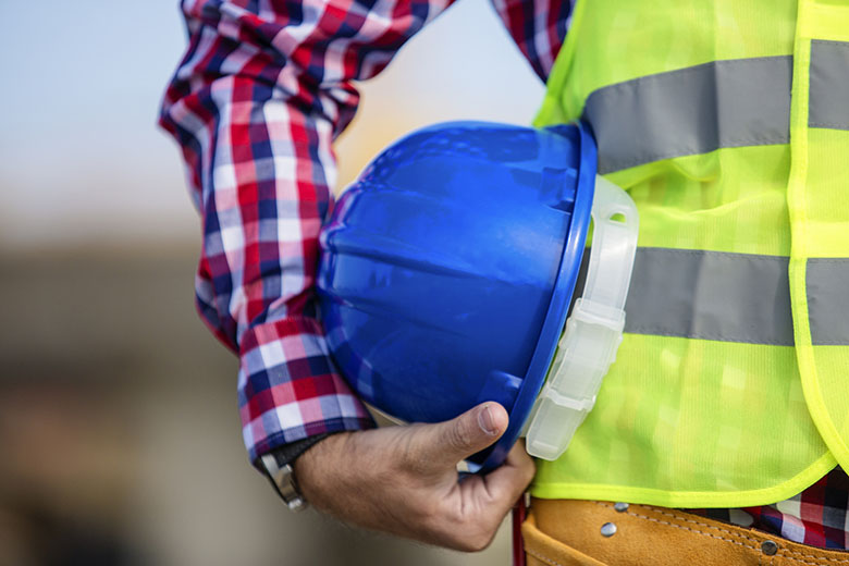 Worker in yellow safety vest holding blue hardhat