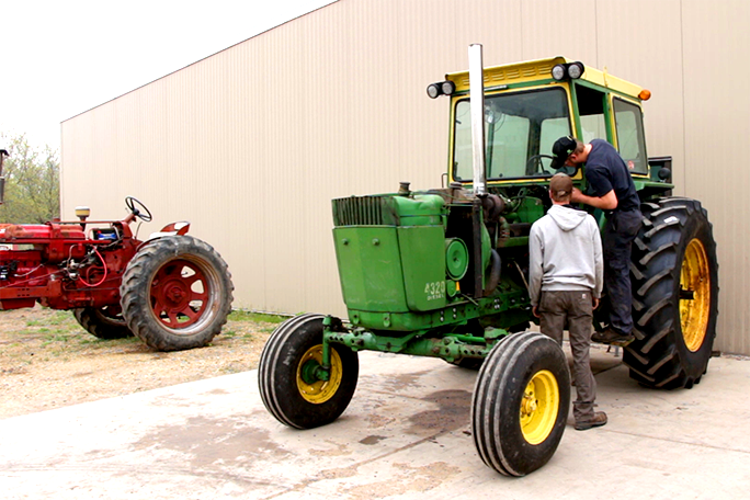 Two students working on a tractor