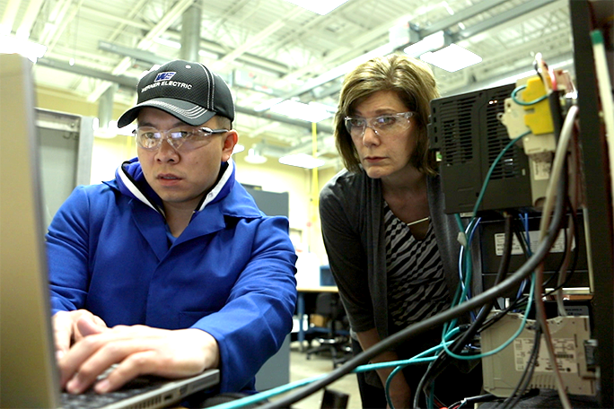 Student and instructor looking at a computer
