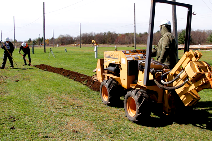 A broadband installer student practicing using heavy machinery that is used in the industry