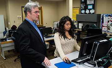 An instructor looking over a student's shoulder on a computer