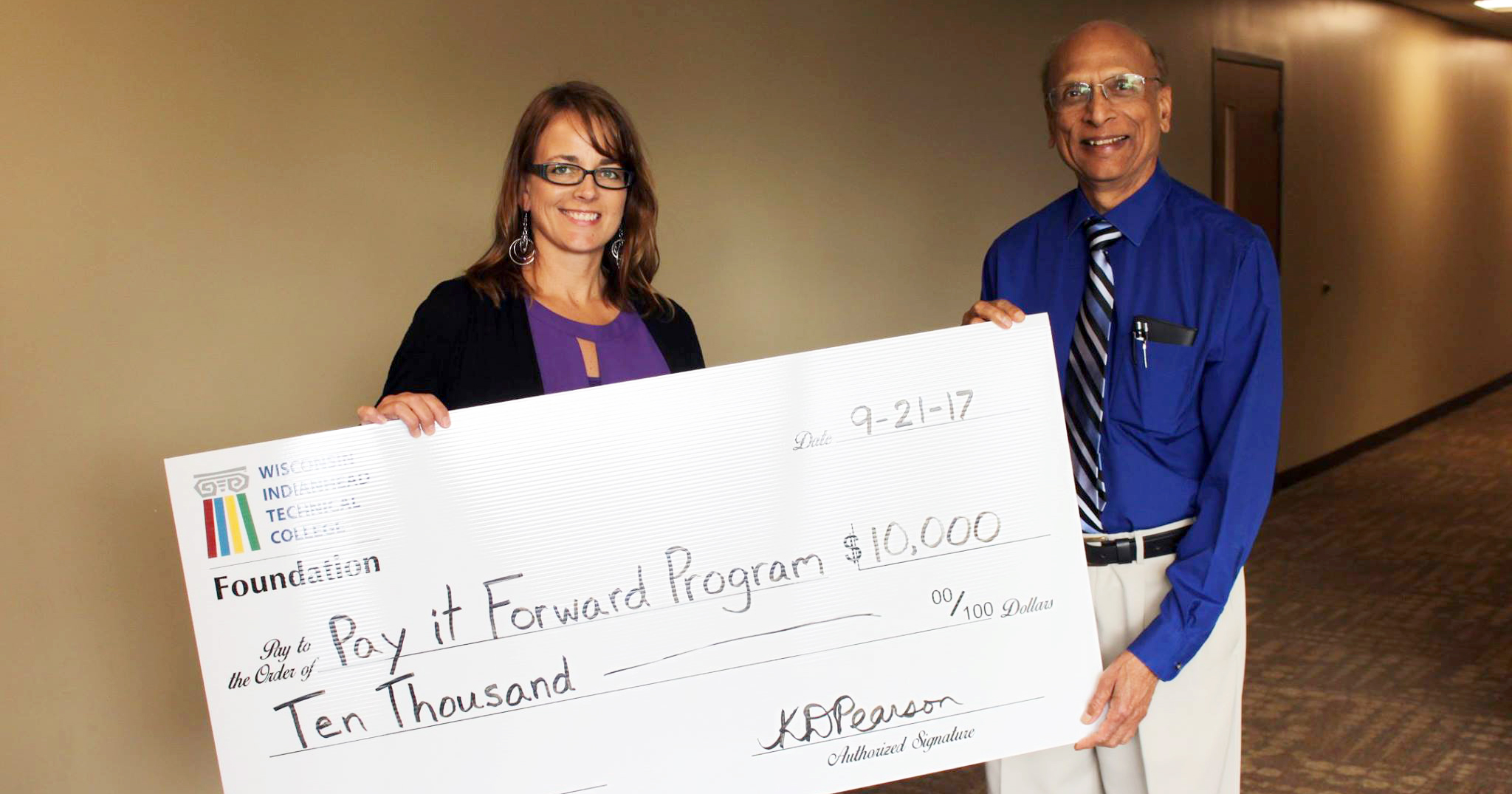 Image of Kim Pearson, Director of College Advancement and Vinod Gupta, donor holding a large $10,000 check